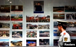 FILE - A paramilitary policeman looks at photos of North Korean leader Kim Jong Un and other North Korea-related images outside the North Korean Embassy in Beijing, Sept. 6, 2012. At the time, an official of a major Chinese investor said China should not be encouraging its companies to invest in reclusive North Korea because it still lacked the conditions to protect foreign investors.