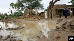 A picture released by Oxfam and taken on17 Aug 2010 shows people standing near homes destroyed by flooding near Zinder