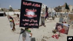 Bendera, foto dan benda-benda lain diletakkan untuk mengenang 21 korban bom bunuh diri di sebuah masjid Syiah terlihat di sebuah taman makam di al-Qudeeh, Arab Saudi (30/5).