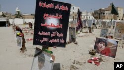 FILE - Religious flags, photographs and tributes to victims of a suicide bombing of a Shi'ite mosque are displayed at a cemetery in al-Qudeeh, Saudi Arabia, May 30, 2015.