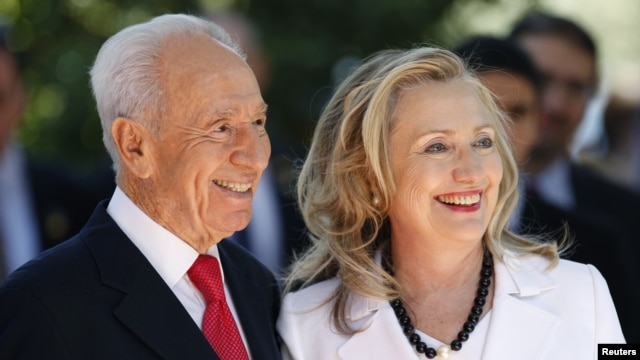 Israel's President Shimon Peres stands with U.S. Secretary of State Hillary Clinton before their meeting in Jerusalem, July 16, 2012