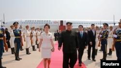 朝鲜领导人金正恩和夫人李雪主2018年6月19日抵达北京,中共中央政治局常委王沪宁迎接。