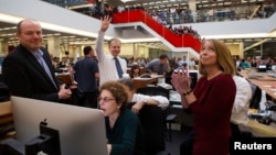 Publisher Arthur Sulzberger Jr. holds up four fingers to indicate the four Pulitzer Prizes won by the New York Times, as winners are announced in the newsroom in New York, April 15, 2013.