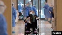 中國湖北武漢一所醫院的醫護人員身穿防護服用輪椅推送一名新冠病毒患者。 (2020年2月10日)