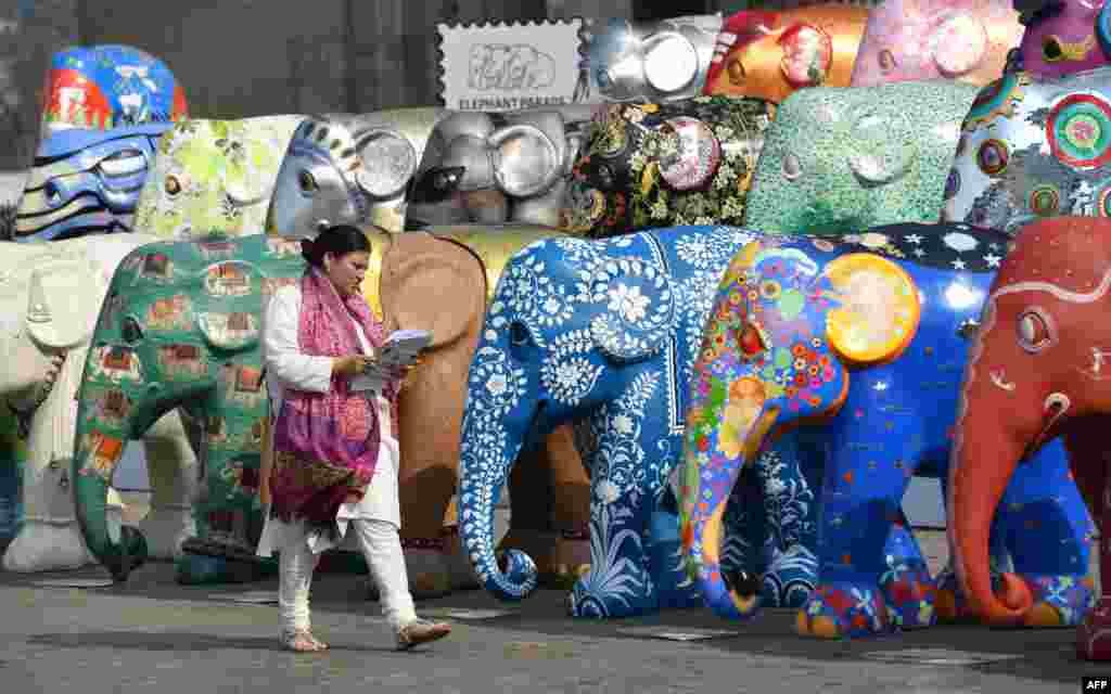 A woman walks among elephant sculptures displayed as part of the Elephant Parade India initiative in Mumbai, India.