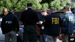 FBI agents work at a scene near the site of Sunday's explosion, March 19, 2018, in Austin, Texas.