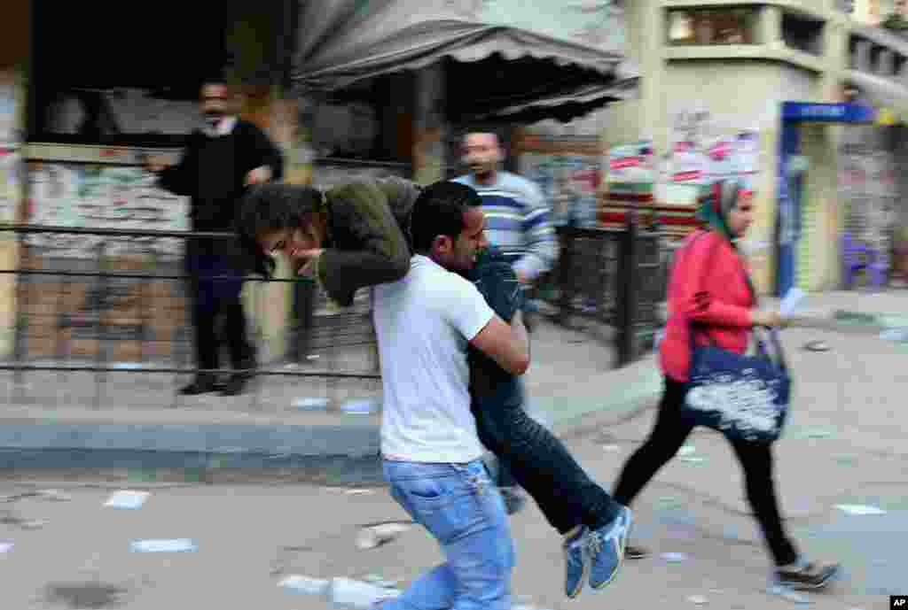 An Alexandria University student carries another student out of the school after she was injured during clashes between student protesters and the Egyptian security forces in Alexandria, March 26, 2014.