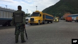 FILE – A National Guard soldier watches over cargo trucks leaving the port Dec. 19, 2016, in Puerto Cabello in Venezuela, the port city that handles the majority of the country's food imports. Across the chain of command, from high-level generals to the lowest foot soldiers, military officials reportedly are using their growing power over the food supply to siphon off wealth for themselves.