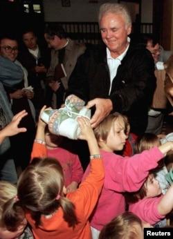 比尔·扬众议员在萨拉热窝的一所孤儿院为波斯尼亚孤儿送鞋。(资料照)