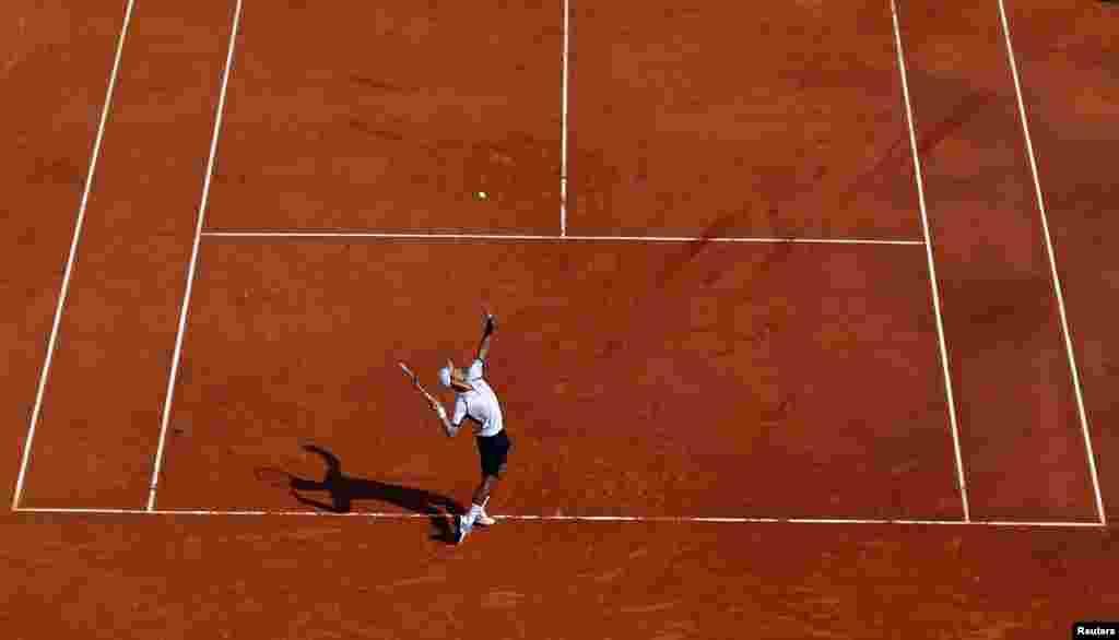 Tay vợt Novak Djokovic của Serbia giao banh cho Juan Monaco của Argentina trong giải Monte Carlo ở Monaco.