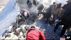 Suriyeliler, Rakka'ya yönelik hava saldırıları sonucu tahrip olan binaların enkazını inceliyor