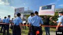 """黃之鋒等抗議人士聚集不夠一分鐘,在場駐守的警員隨即警告他們違反4人以上公眾聚集的""""限聚令"""",並且拉起封鎖線將他們包圍截查,向他們發出約260美元的定額罰款告票。(美國之音湯惠芸拍攝)"""