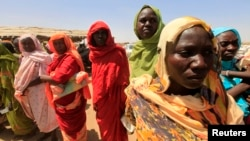Displaced women wait to receive food at a food distribution center as special envoys and diplomats arrive for a meeting to discuss the progress of a peace treaty in Darfur, at Shangli Tobay village in North Darfur, June 18, 2013.