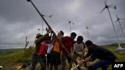Warga menegakkan kincir angin di lapangan turbin angin kecil di desa di Pulau Sumba, Nusa Tenggara Timur. (Foto: AFP)