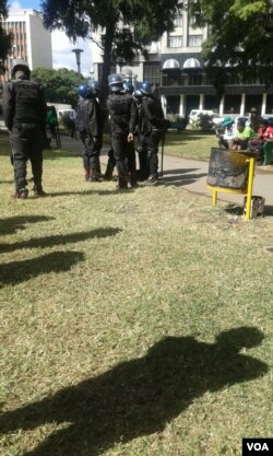 Police attempt to remove protesters from Africa Unity Square in Harare.