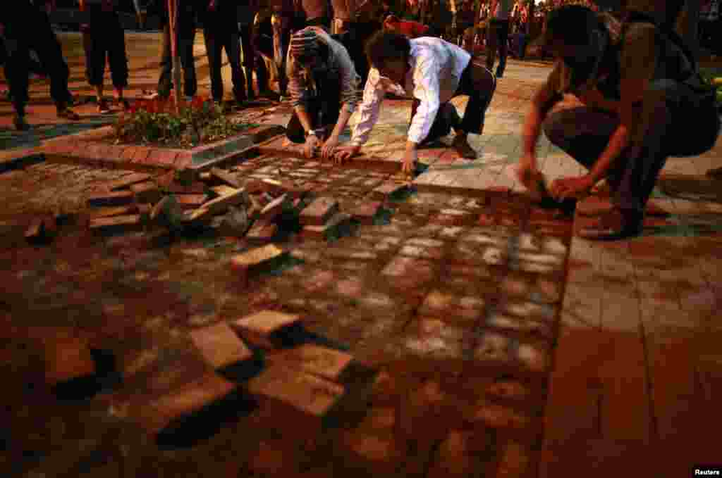 Anti-government protesters remove bricks from a sidewalk to build a barricade in central Ankara, June 9, 2013.