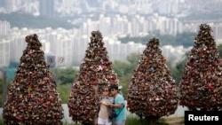 Sepasang kekasih mengambil swafoto atau selfie di atas bukit Namsan di pusat kota Seoul, Korea Selatan. (Reuters/Kim Hong-Ji)