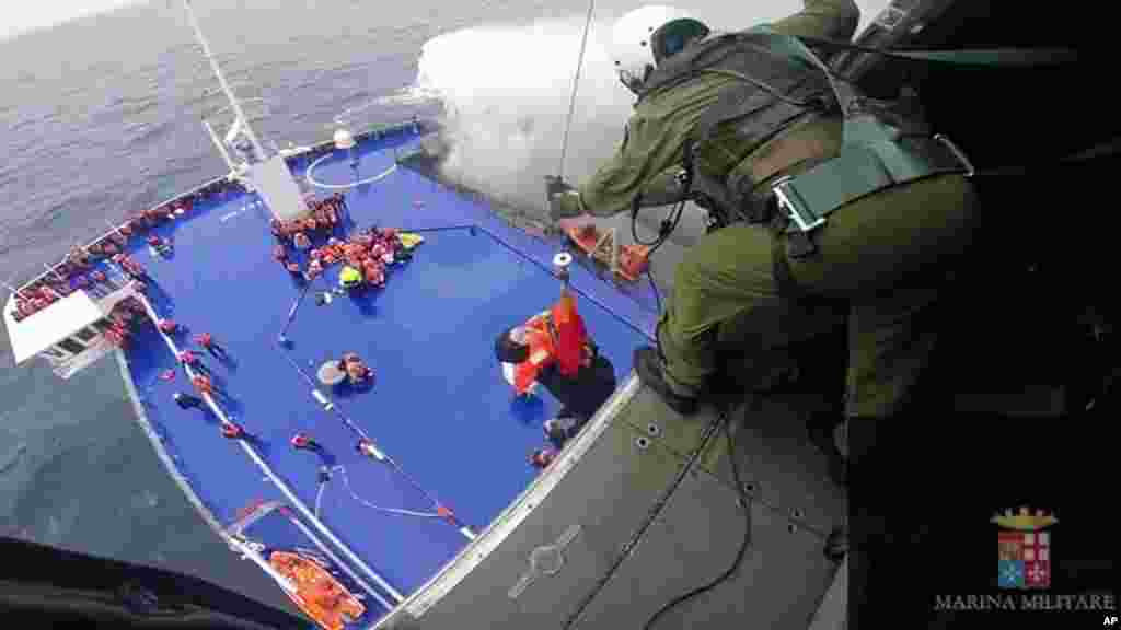 In this image taken from video and released by the Italian Navy, a woman is lifted from the deck of the Italian-flagged ferry Norman Atlantic by a rescue helicopter after it caught fire in the Adriatic Sea, Dec. 28, 2014.