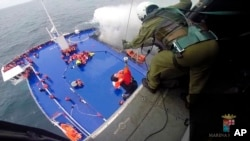 Một phụ nữ được kéo lên trực thăng từ chiếc phà bị cháy ở biển Adriatic, ngày 28/12/2014.