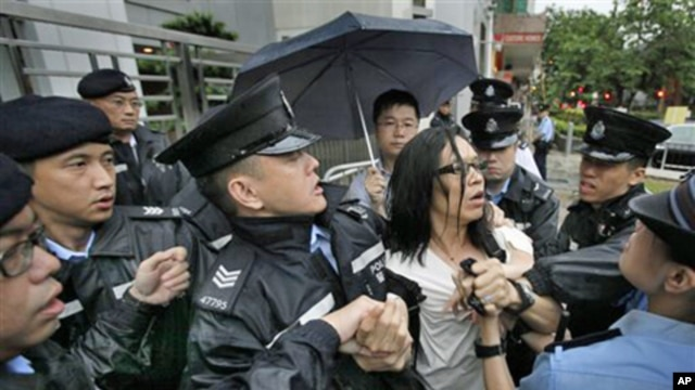 A protester scuffles with police officers who were trying to stop a fellow demonstrator from throwing a bag of tofu during a protest to support Chinese dissident Tan Zuoren at the Chinese government's liaison office in Hong Kong, 9 June 2010.