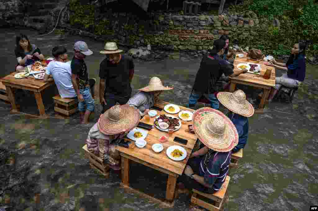 Customers eat lunch at a restaurant with tables in a stream in Kampung Kemensah on the outskirts of Kuala Lumpur, Malaysia.