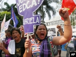 Protesters hold signs denouncing the Enhanced Defense Cooperation Agreement (EDCA) during a protest outside the Supreme Court in Manila on Jan. 12, 2016.