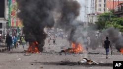Congo Violence: People walk near burning debris during election protests in Kinshasa, Democratic Republic of Congo, Monday, Sept. 19, 2016.