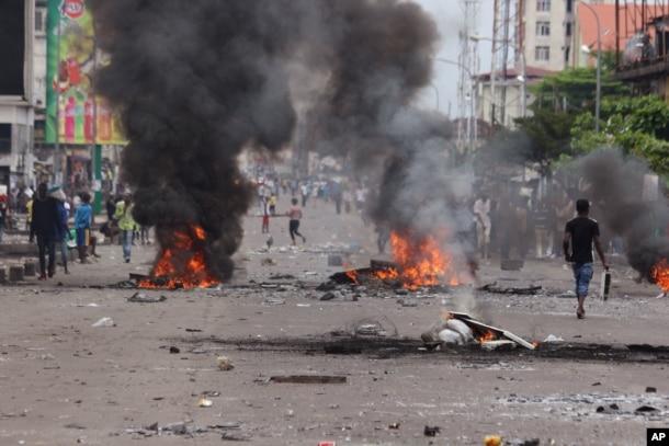 People walk near burning debris during election protests in Kinshasa, Democratic Republic of Congo, Monday, Sept. 19, 2016.