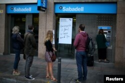 People line up at a Sabadell Bank ATM machine in Barcelona to withdraw money as part of a protest of the transfer of the bank's headquarters out of Barcelona, Spain, Oct. 20, 2017.