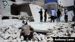 Mideast Syria: This photo provided by the Syrian Civil Defense group known as the White Helmets, shows members of Civil Defense inspecting damaged buildings after airstrikes hit the Bustan al-Qasr neighborhood of Aleppo, Syria, Sunday, Sept. 25, 2016.