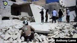 지난 25일 시리아 알레포의 반군 장악 지역인 부스탄알카스르에서, 민방위대 '화이트헬멧' 대원들이 공습으로 무너진 건물 잔해를 살피고 있다.