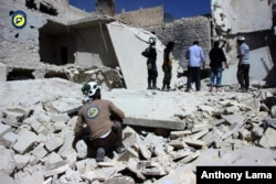 Civil Defense members inspect damaged buildings after airstrikes hit the Bustan al-Qasr neighborhood of Aleppo, Syria, Sept. 25, 2016.