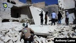 Abaharanira agateka ka muntu muri Siriya batohoza ivyasenyuwe n'ibitero vy'indege i al-Qasr mu micungararo ya Aleppo.
