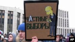 12月24日在大示威中手举漫画的抗议者,漫画上面写道:普京把诚实选举变成个人选举