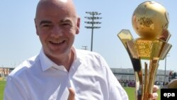 """Le président de la FIFA, Gianni Infantino, tient un trophée dedies aux """"travailleurs de la Coupe du au Qatar 2016"""" à Doha, Qatar, 22 avril 2016. epa/ STRINGER"""