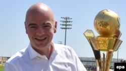 """Le président de la FIFA, Gianni Infantino, tient un trophée dediés aux """"travailleurs de la Coupe du au Qatar 2016"""" à Doha, Qatar, 22 avril 2016. epa/ STRINGER"""