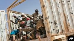 Les migrants montent dans un camion pour se diriger vers le nord en Algérie au poste frontière d'Assamaka, dans le nord du Niger, le 3 juin 2018.