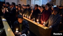 Worshipers hold candles during a mass on the eve of Easter, at a catholic church in Taiyuan, Shanxi province. March 30, 2013.