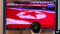 FILE - Footage of a parade in Pyongyang featuring a giant North Korean flag is seen at a TV screen during a news program reporting on North Korea, at the Seoul Railway Station, in Seoul, South Korea, Oct. 10, 2020.