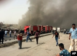 Smoke rises as Iraqi security forces and civilians gather at the scene of a deadly suicide car bomb attack in the Shiite-dominated neighborhood of New Baghdad, Iraq, Thursday, June 9, 2016.