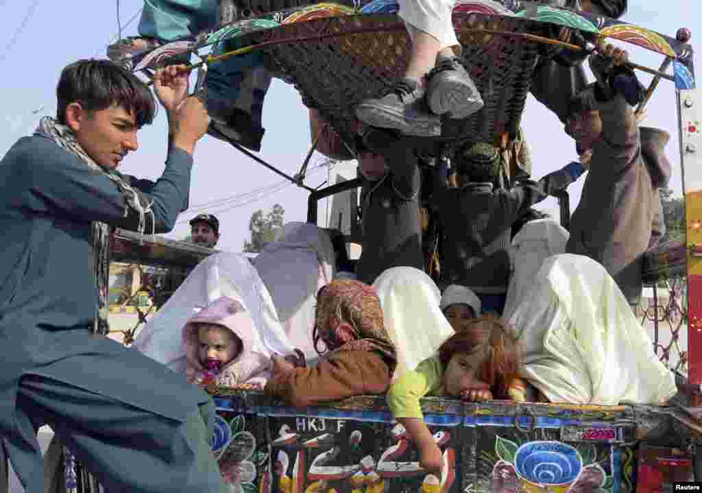 Families sit at the back of a van with their belongings while fleeing a military offensive against the Pakistani Taliban, as they enter Bannu in Khyber Pakhtunkhwa province, Jan. 22, 2014.