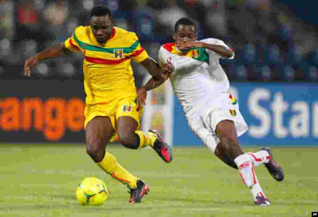 Mali's Tamboura challenges Guinea's Traore during their African Nations Cup Group D soccer match at Franceville Stadium
