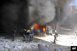 In this photo released on Feb. 20, 2018 provided by the Syrian Civil Defense group known as the White Helmets, shows members of the Syrian Civil Defense extinguishing a store during airstrikes and shelling by Syrian government forces, in Ghouta, a suburb of Damascus, Syria