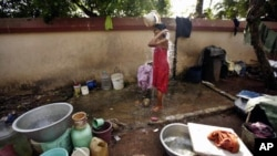 A woman bathes using water collected from various areas on World Water Day at a slum in Bhubaneswar, India, March 22, 2012.