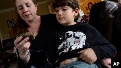 Heidi Elbarky memberikan insulin kepada anak laki-lakinya, Omar, 8 Tahun, di kediamannya di Spring Hill, Tennessee, 12 Maret 2014.