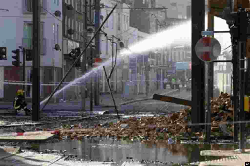 A firefighter sprays water onto the furniture store set on fire by rioters last night in Croydon, south London, Tuesday, Aug. 9, 2011. A wave of violence and looting raged across London and spread to three other major British cities Tuesday, as authoritie