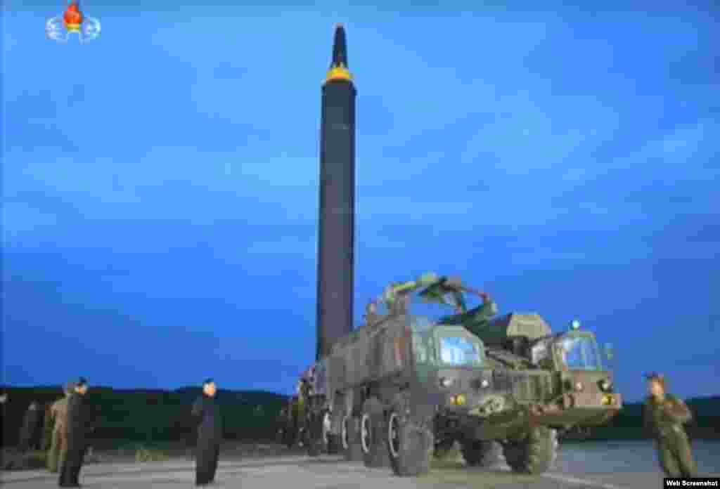 북한 '조선중앙TV'가 지난 29일 평양 순안공항에서 실시한 '화성-12' 탄도미사일 발사훈련 사진들을 공개했다. 김정은 국무위원장(왼쪽)이 이동식발사대에서 수직으로 세워진 미사일을 보고 있다. 우리민족끼리 웹사이트 영상 캡쳐.