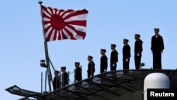 FILE - Sailors stand on the deck of the Izumo warship as it departs from the harbor of the Japan United Marine shipyard in Yokohama, south of Tokyo.