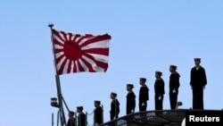2015年3月25日,日本海军站在即将起航的出云级护卫舰甲板上,这艘军舰即将驶离东京南部的横滨日本联合海上造船厂。