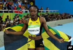 Jamaica's Elaine Thompson celebrates with the Jamaican flag after winning gold in the women's 100-meter final during the athletics competitions in the Olympic stadium of the 2016 Summer Olympics in Rio de Janeiro, Brazil, Saturday, Aug. 13, 2016.